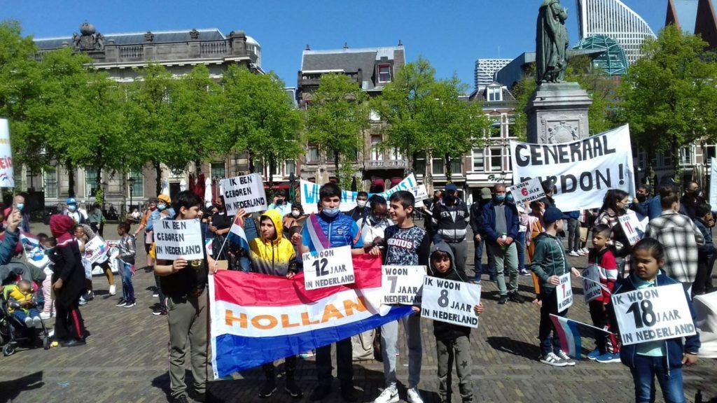 Overzicht van een deel van de deelnemers aan de actie. Mensen dragen bordjes waar op staat hoe lang ze in Nederland zijn.