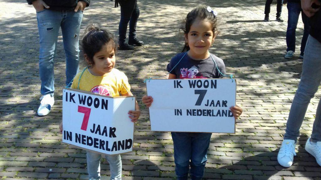 Twee kinderen met elk bordjes waar op staat dat ze al zeven jaar (hun hele leven?) in Nederland zijn.