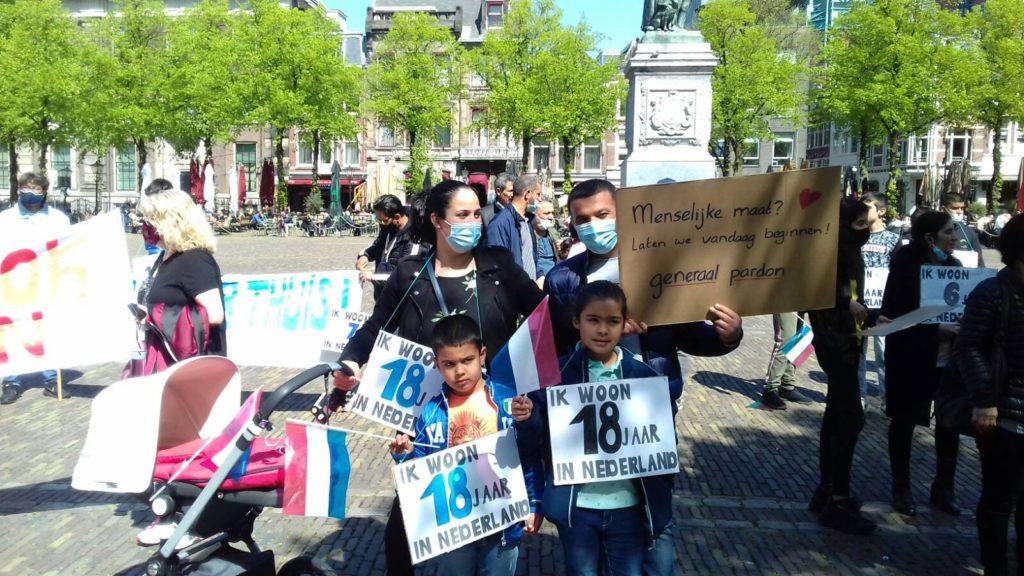 """Een gezin bij de demonstratie, ze dragen een bord met de tekst: """"Menselijke maat? Laten we vandaag beginnen! Generaal pardon."""""""