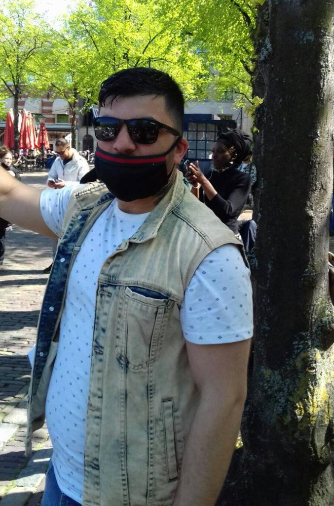 Eén van de organisatoren. Hij draagt een wit shirt, een denim jack en een zwart mondkapje.