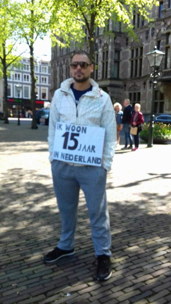 Een deelnemer met een bord waar op staat dat hij 15 jaar in Nederland woont.
