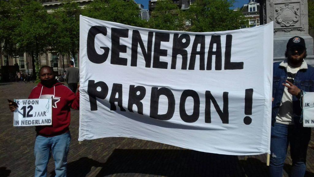 """Twee demonstranten met een spandoek met de tekst """"Generaal pardon!""""."""