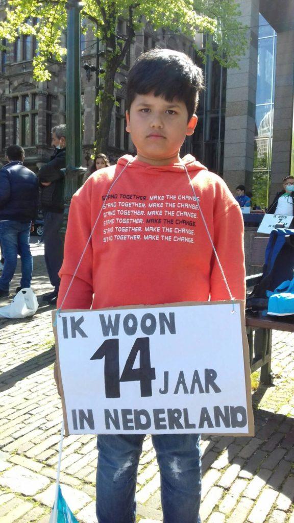 """Kind met een bord """"Ik woon 14 jaar in Nederland""""."""