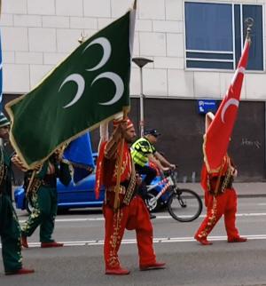 Grijze Wolven-symbolen voorop tijdens de optocht: een groene en een rode vlag met drie halve manen.
