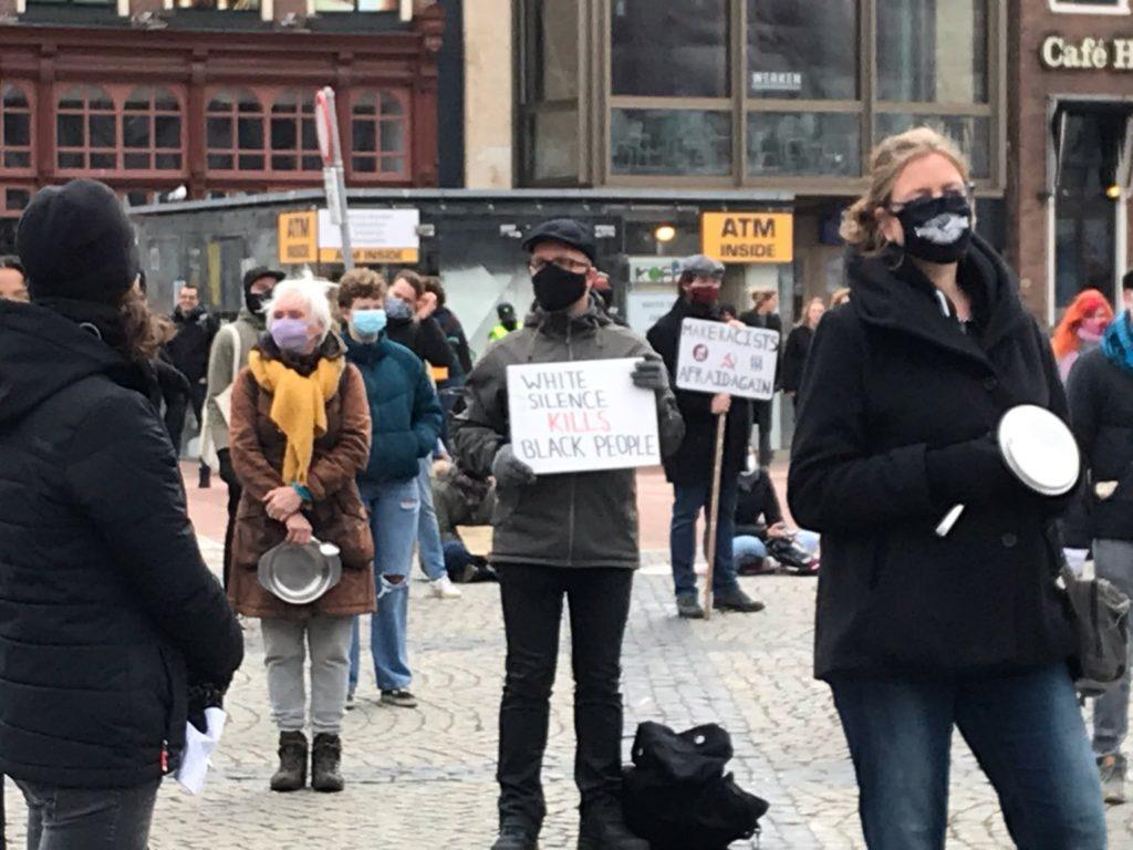 """Mensen op de Grote Markt in Groningen. In het midden een witte man met een pet en een bord met de tekst """"White silence kills black people""""."""