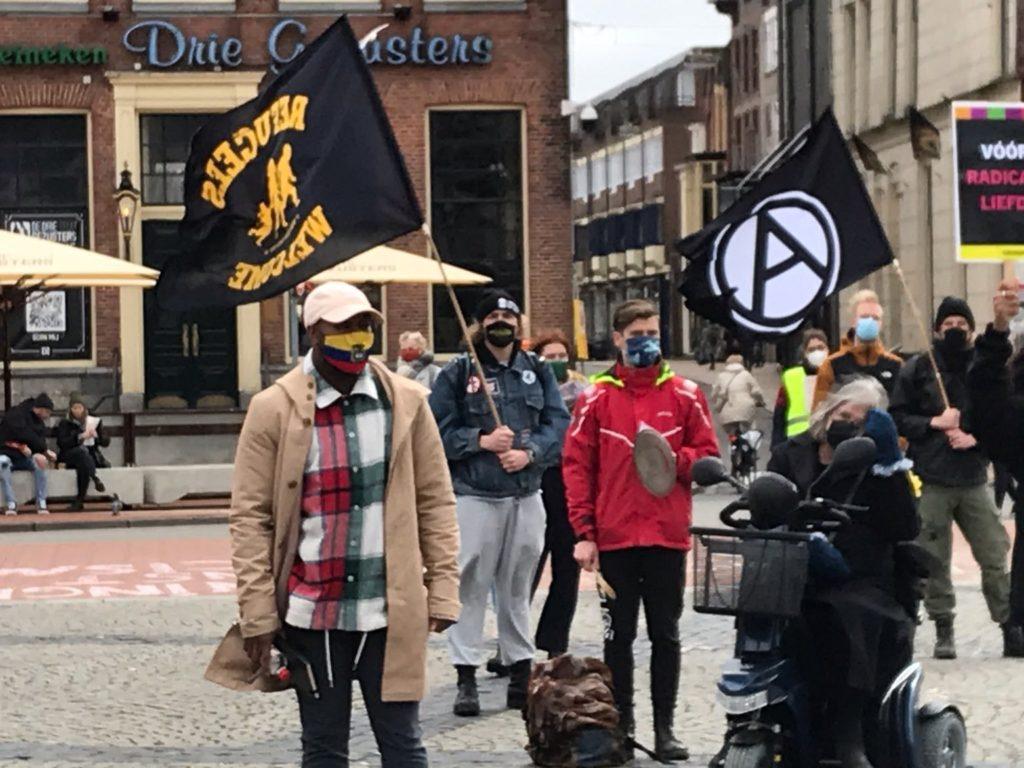 Groepje demonstranten in Groningen. Grote, zwarte anarchisme-vlag, 'Refugees welcome'-vlag, persoon in een scootmobiel.