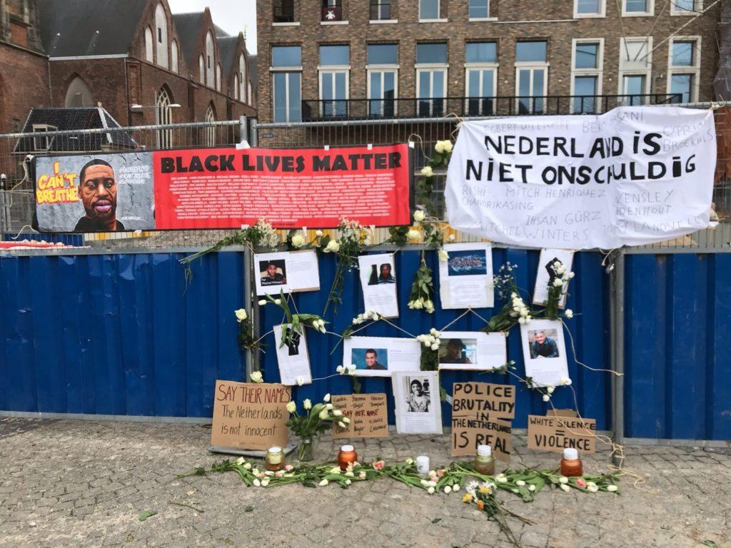 """Een bouwhek met daarop foto's van Nederlandse zwarte personen / personen van kleur die zijn omgekomen door politiegeweld, waaronder Mitch Henriques en Tomy Holten. Er hangt een spandoek met de tekst """"Nederland is niet onschuldig"""" en de namen van slachtoffers van politiegeweld, waaronder Rishi Chandrikasing en Ihsan Gürz."""