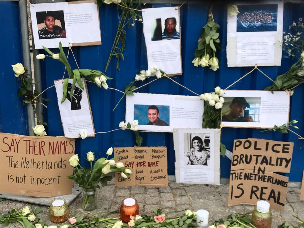 Een foto dichterbij van het eerder genoemde bouwhek met foto's van slachtoffers van politiegeweld. Er staan kaarsjes bij en overal zijn witte tulpen en witte rozen.