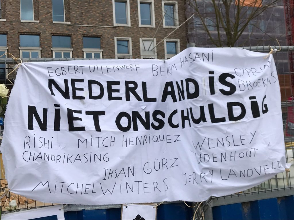 Een close-up van het spandoek met namen van slachtoffers van politiegeweld in Nederland. De namen die zichtbaar zijn op de foto: Cyprian Broekhuis, Rishi Chandrikasing, Mitch Henriquez, Ihsan Gürz, Wensley Udenhout, Mitchel Winters, Jerry Landveld.