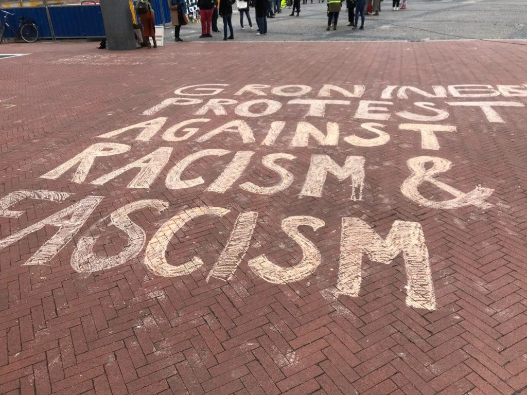 """Grote stoepkrijttekst """"Groningen protest against racism & fascism""""."""