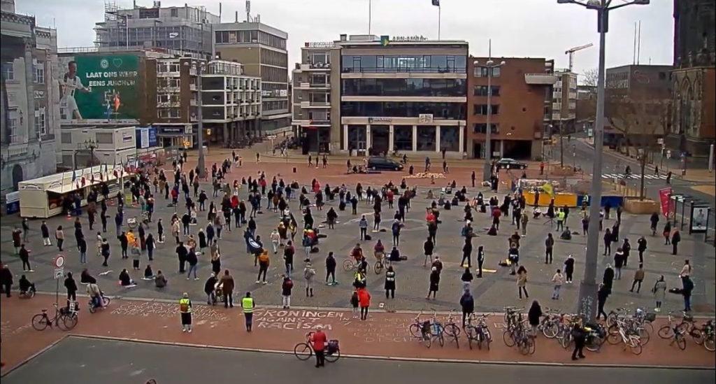 Overzicht van het protest in Groningen, van een afstand en vanuit een hoge positie genomen. Je ziet tientallen mensen die gelijkmatig verspreid staan.