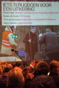 Wandprojectie met de sprekers en daaronder dwangarbeiders.
