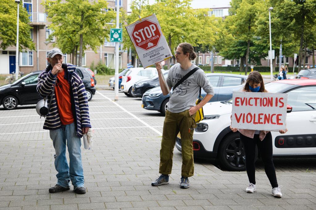 """Iemand spreekt de demonstranten toe via een megafoon. Twee anderen staan ernaast met borden met """"Stop huisuitzettingen"""" en """"Eviction is violence""""."""