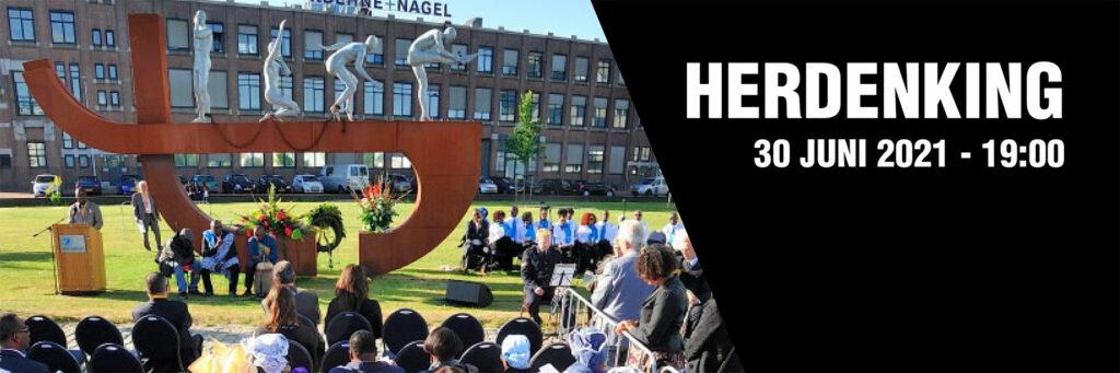 Foto van een vorige herdenking bij het Rotterdamse slavernijmonument met de aankondiging van de herdenking 2021.