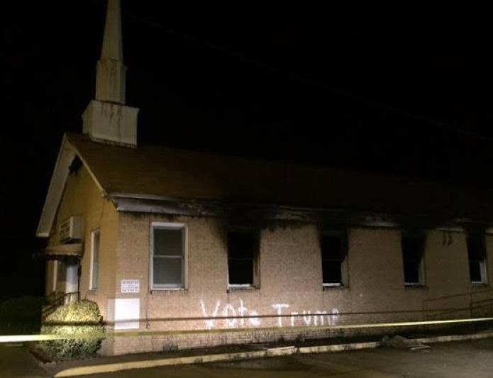 De uitgebrande kerk, met leus erop.
