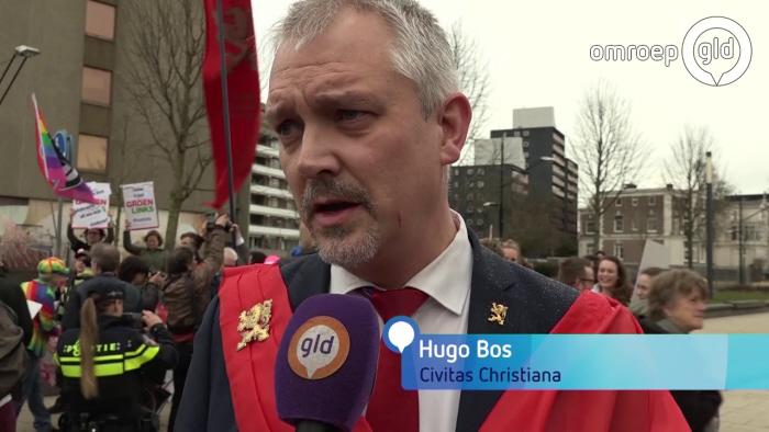 Civitas-baas Hugo Bos bij het protest in NIjmegen, links op de achtergrond de tegendemonstranten.