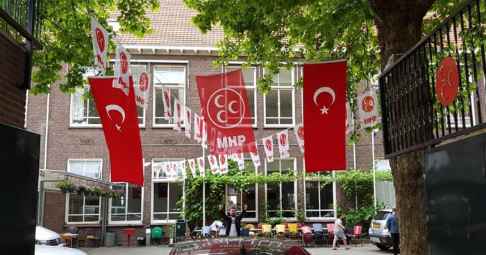 """Voorbereidingen bij de TICS voor het bezoek van ATK-leider Cemal Çetin vooraf aan de Turkse verkiezingen. Let op de vele MHP-vlaggen en het MHP-logo op het hek. Çetinkaya noemt hem op zijn Facebook-pagina """"mijn dierbare president""""."""