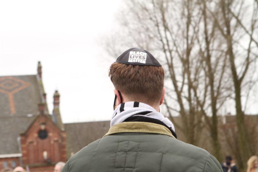 Een persoon met een keppel met daarop de tekst 'black lives matter'.