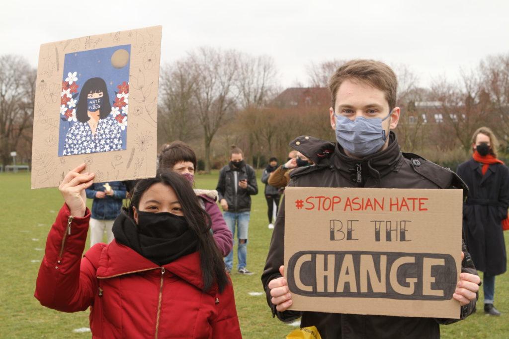 """Een Aziatisch persoon met lange haren houdt een bord omhoog met daarop een kleurrijke afbeelding van een Aziatisch persoon met een mondkapje met de tekst """"Hate the virus"""". Naast haar staat een wit persoon met korte haren en een bord met de tekst """"Stop Asian hate - be the change""""."""