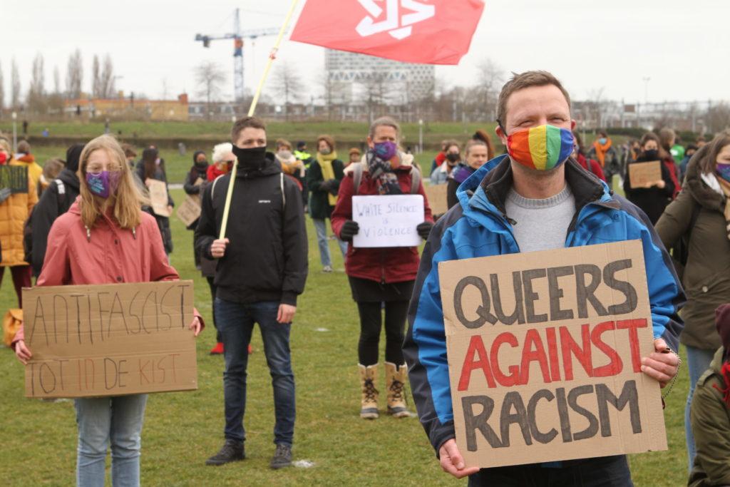 Een persoon met een regenboogmondkapje en een bord met de tekst 'Queers against racism'. Iets verder naar achteren een persoon met een roze jas en een bord met de tekst 'Antifascist tot in de kist'.