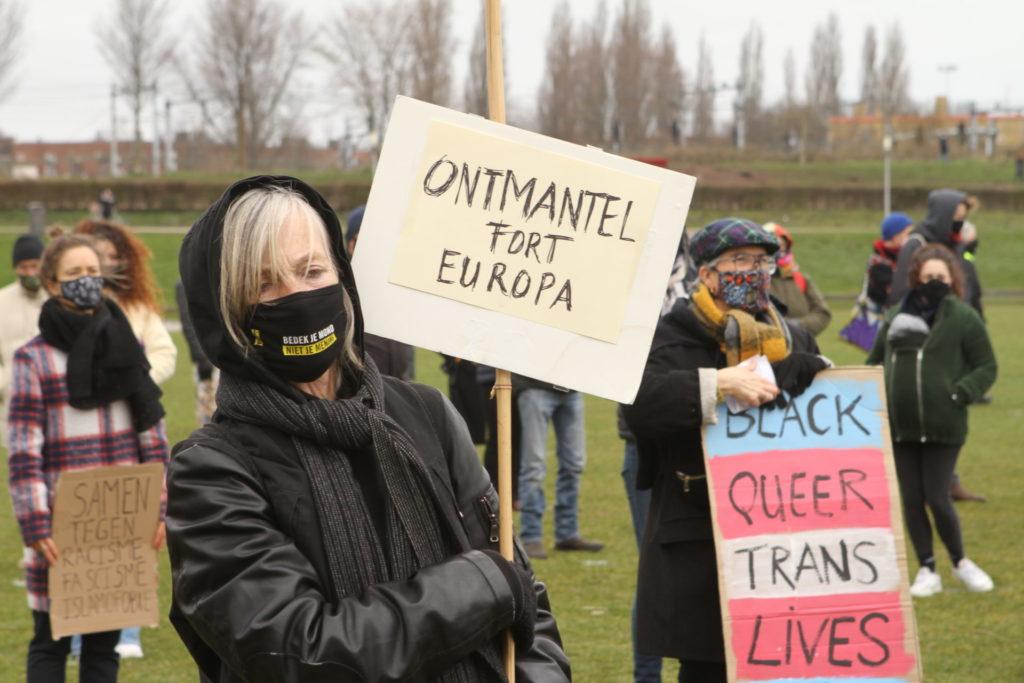 """Een persoon in het zwart, met een mondkapje met de tekst """"Bedek je mond, niet je mening"""" en een bord met de tekst """"Ontmantel Fort Europa"""". Op de achtergrond een persoon met een kleurige pet en een bord in de kleuren van de transvlag met de tekt """"Black queer lives""""[matter]""""."""
