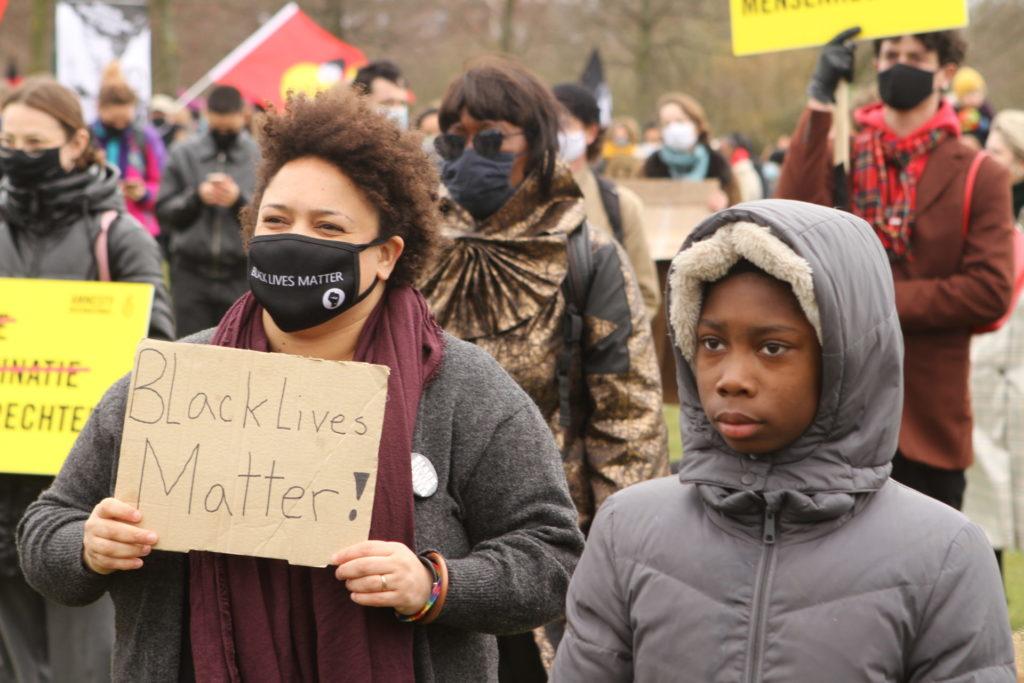 """Een zwart kind en een zwarte volwassene naast elkaar. Het kind kijkt ernstig. De volwassene draagt een bord met de tekst """"Black lives matter""""."""