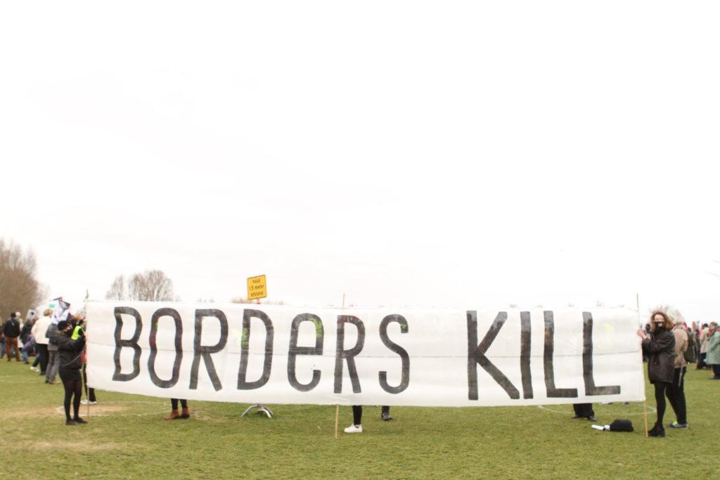 """Een enorm spandoek van misschien wel zes of zeven meter breed, vastgehouden door twee personen, met in hele grote letters de tekst """"Borders kill""""."""