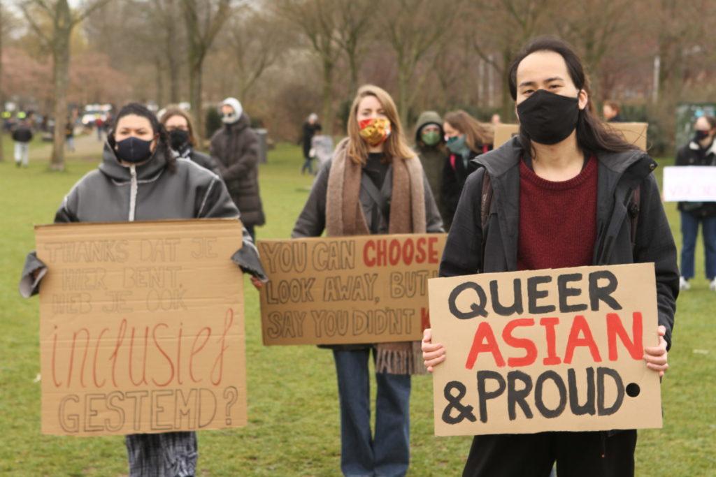 """Drie personen poseren met hun borden voor de foto. Twee borden zijn goed leesbaar met de volgende teksten:  """"Thanks dat je hier bent, heb je ook inclusief gestemd?""""  """"Queer, Asian & proud""""."""