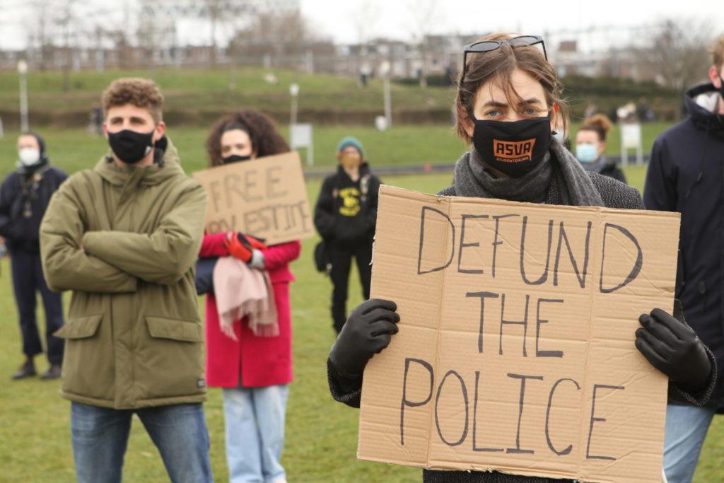 """Een persoon met een bord met de tekst """"Defund the police""""."""
