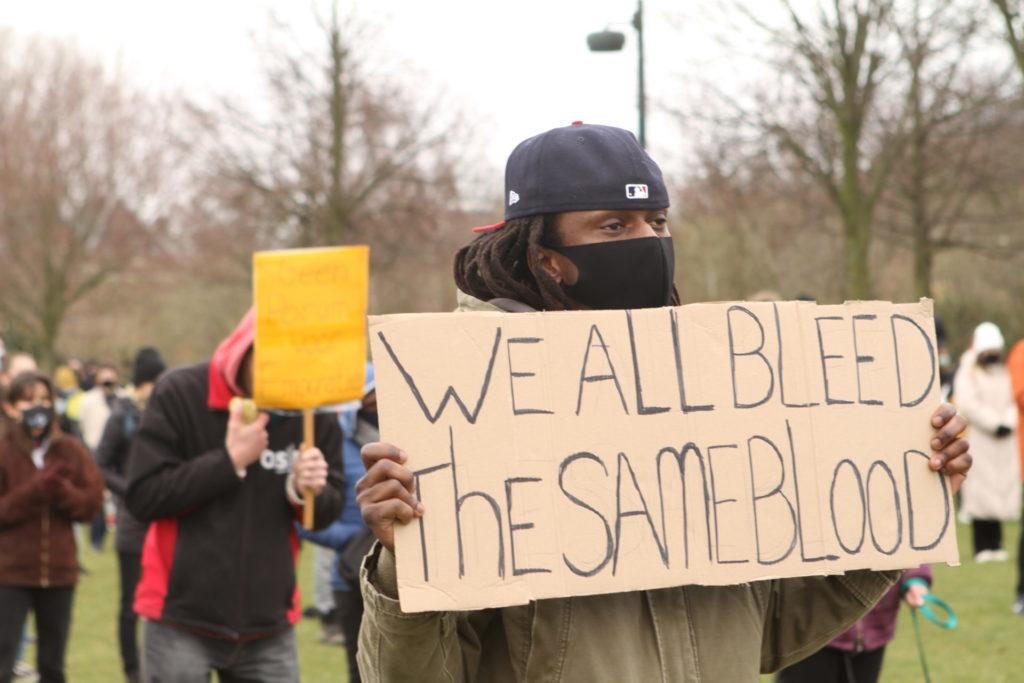 """Een persoon met een bord met de tekst """"We all bleed the same blood""""."""
