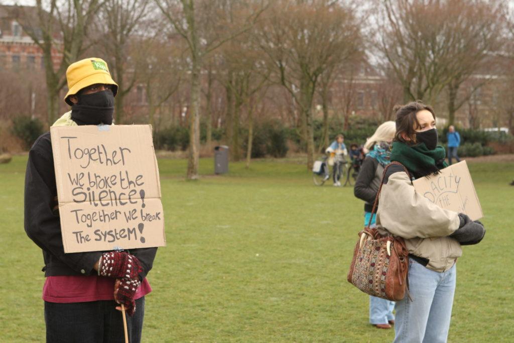 """Twee personen waarvan eentje met een bord met de tekst """"Together we broke the silence! Together we break the system!""""."""