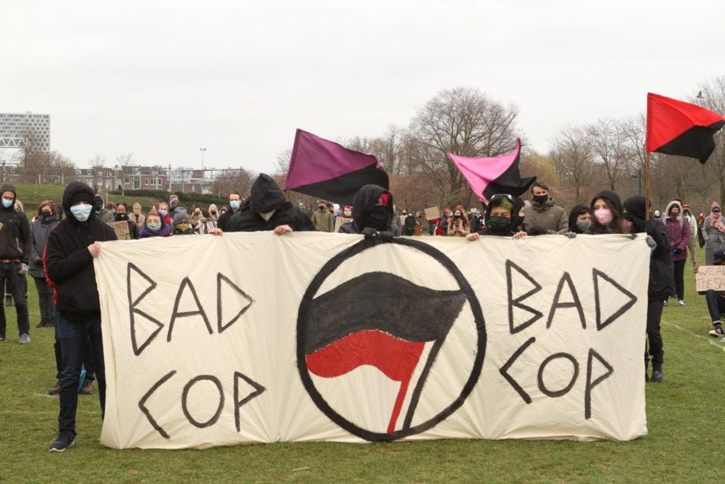 """Vier in het zwart gekleden personen met een groot spandoek met antifa-logo met de tekst """"Bad cop bad cop""""."""