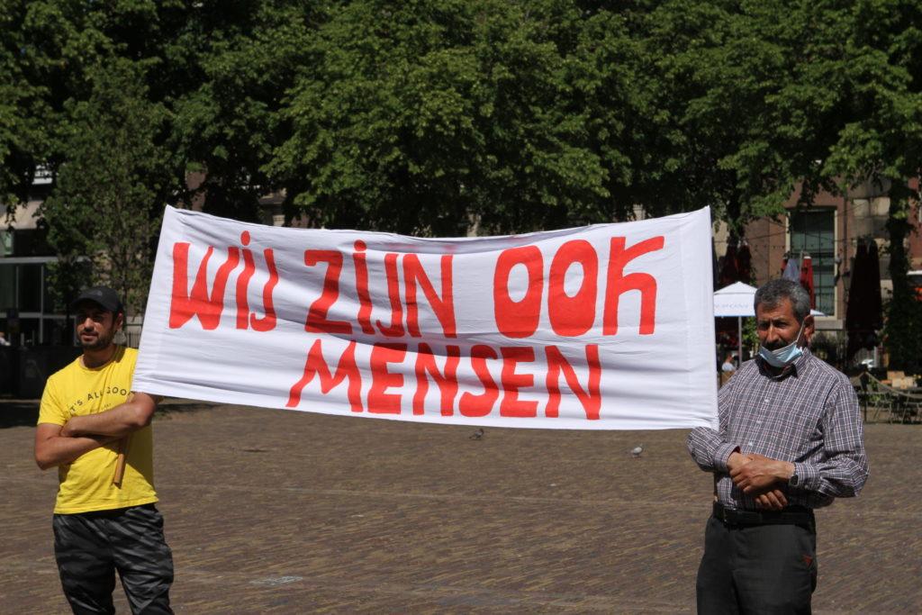 """Twee demonstranten met een spandoek met de tekst """"WIJ ZIJN OOK MENSEN""""."""