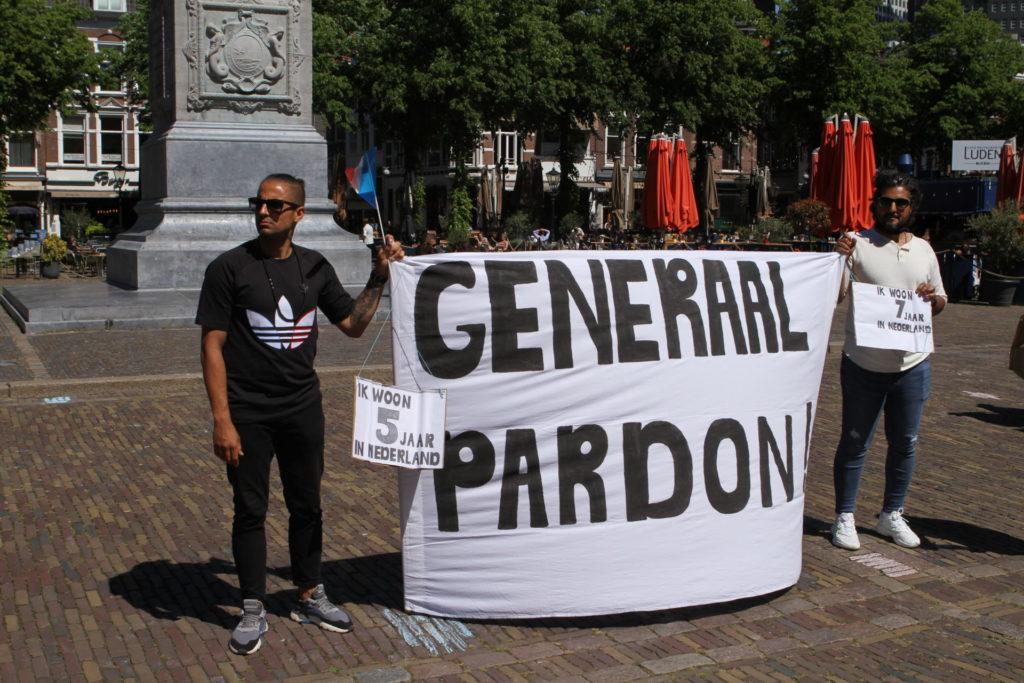 Twee demonstranten met een groot spandoek met de tekst 'GENERAAL PARDON'.