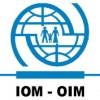 Logo van de IOM, met de afbeelding van gezinnetje dat 'vrijwillig' gedeporteerd wordt.