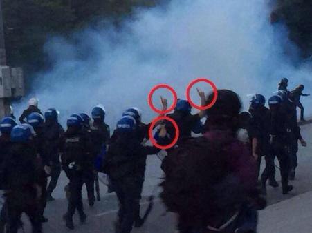Turkse agenten maken voordat ze met scherp gaan schieten op Koerdische demonstranten een IS-teken.