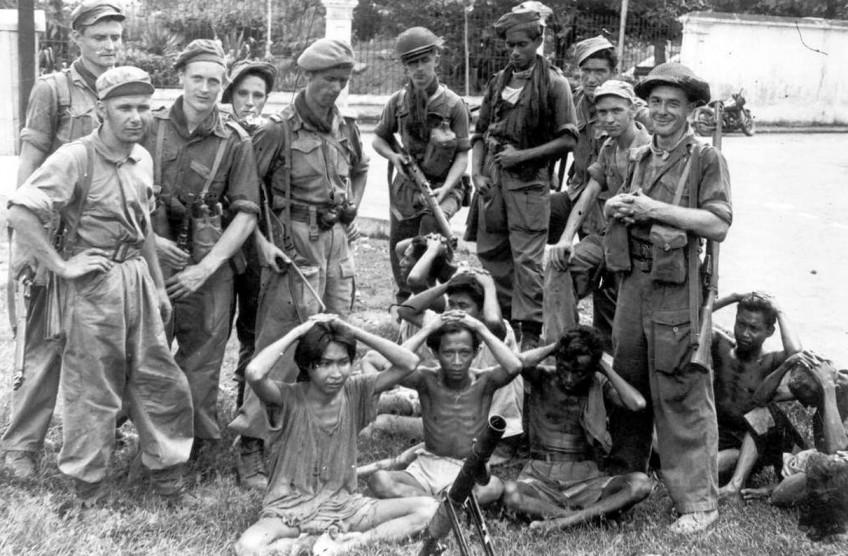 Een zwartwitfoto waarop Nederlandse soldaten een aantal Indonesische gevangenen onder schot houten. De gevangenen zitten allemaal met hun handen op het hoofd. De soldaten staan er opvallend relaxed bij, eentje heeft zelfs een brede grijns op zijn gezicht.