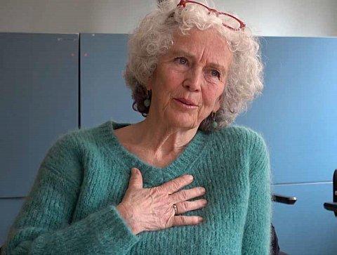 Kea Vogelberg. Ze draagt een pluizige turquoise gebreide trui en ze heeft een bos grijze krullen. IN haar haar een rode leesbril. Ze heeft haar rechterhand op haar borst. Aan haar ringvinger zit een goudkleurige ring.