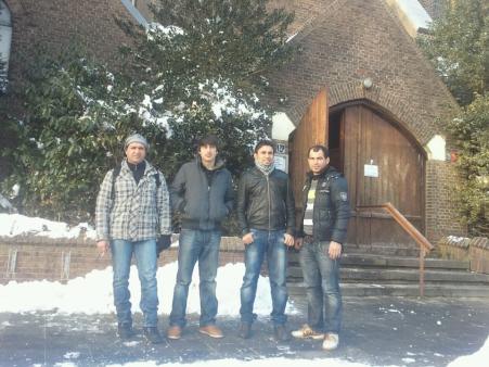 Vier vluchtelingen voor de gekraakte kerk.