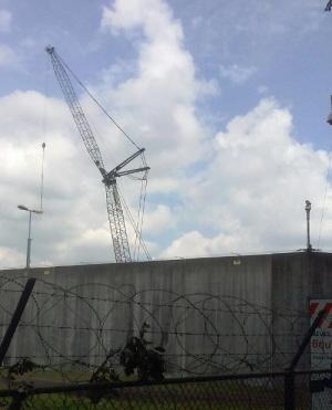 Een bouwkraan achter de muren van Kamp Zeist.