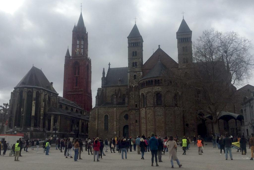 Het Vrijthof in Maastricht, guur weer. Je ziet de kerk en de basiliek met daarvoor tientallen demonstranten.