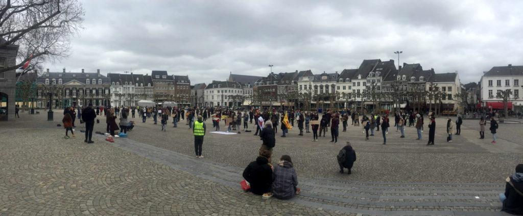 Overzichtsfoto van de demonstratie op het Vrijthof. Op de voorgrond trappetjes waar enkele mensen op zitten. Daarachter allemaal staande demonstranten.