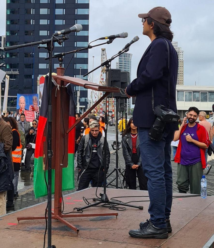 Massoud spreekt de demonstranten toe vanachter een lessenaar waar een Afghaanse vlag aan hangt. Massoud draagt een bruin petje, een blauw jasje en een spijkerbroek.