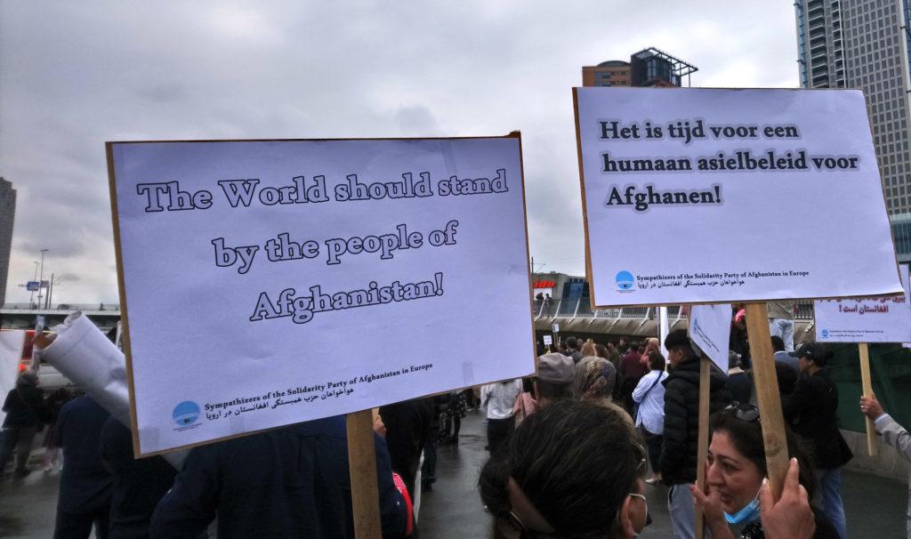 Twee borden, teksten: 'The world should stand by the people of Afghanistan' en 'Het is tijd voor een humaan asielbeleid voor Afghanen!'.