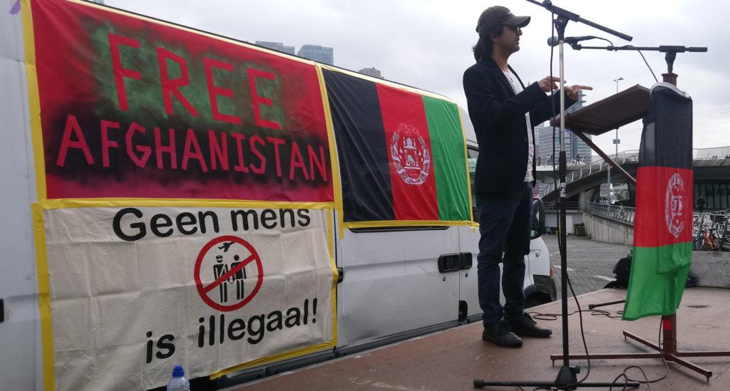 Massoud op het podium met achter zich de bus met spandoeken, teksten 'Free Afghanistan' en 'Geen mens is illegaal!'.