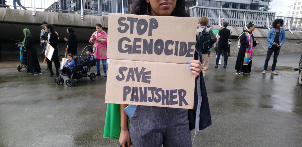 Protestbord met de tekst 'Stop genocide - save Panjsher'.