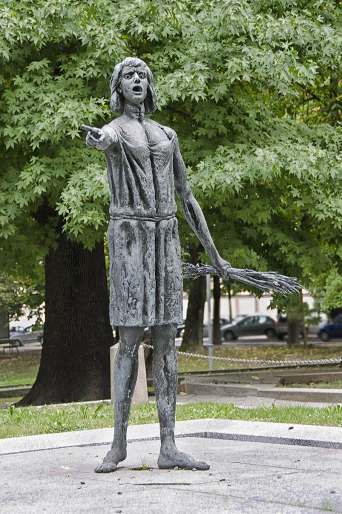 Bronzen beeld van een persoon in een eenvoudige jurk met een touwje om hun middel, op blote voeten en met een bos takken in een hand. De persoon wijst naar iets en lijkt boos te schreeuwen.