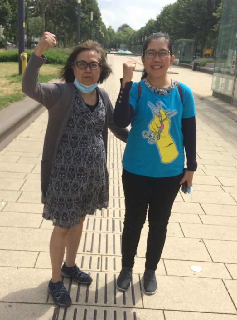 Twee deelnemers aan de demonstratie, beide met de vuisten in de lucht. Eentje draagt een T-shirt met daarop een hand gehuld in een schoonmaakhandschoen die een bos sleutels vasthoudt.