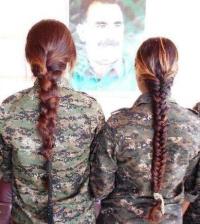 Koerdische strijdsters kijken naar een portret van Öcalan.