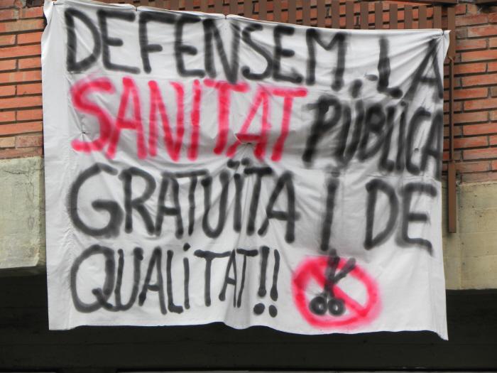 """Laken uit een raam in Olot (Catalonië) in 2013 met de tekst: """"Verdedig de publieke gezondheidszorg: gratis en kwaliteit"""". (foto: Ellen de Waard)"""
